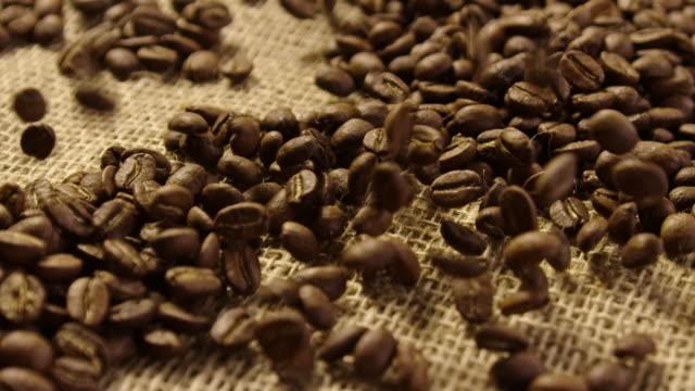 スローモーション 4 k で落ちるコーヒー豆のクローズ アップ - 麻袋点の映像素材/bロール