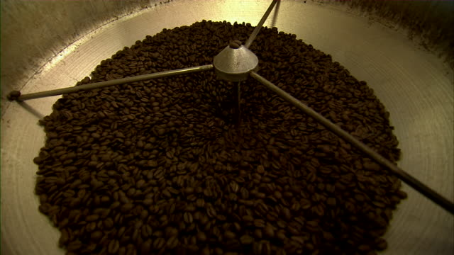 Close up of coffee beans moving through grinder.