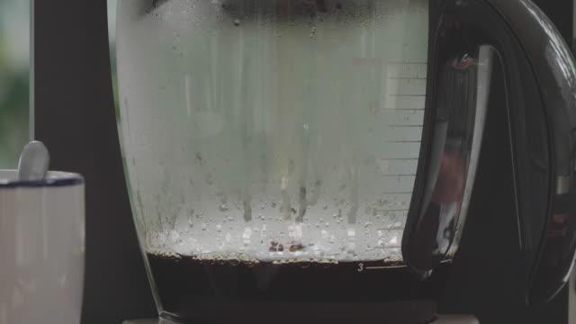 close up of coffee being brewed in coffee maker. - bricco per il caffè video stock e b–roll