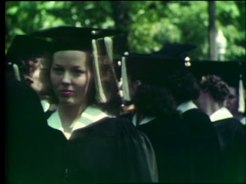 vidéos et rushes de close up of college students in cap and gowns passing camera / graduation / outdoors / university of missouri - 1950