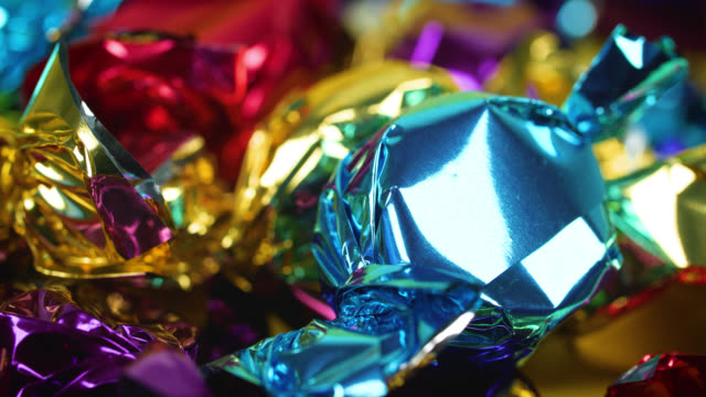 Close up of colourful toffee wrappers glistening in the light