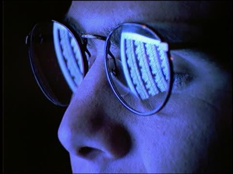 vídeos de stock e filmes b-roll de blue close up of computer screen reflected in businessman's eyeglasses - cinematografia