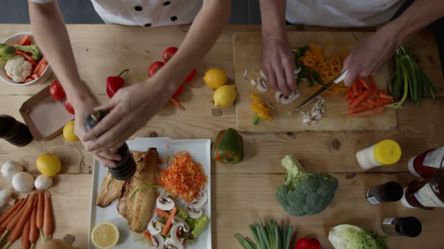 自宅で一緒に調理し、食べ物を味付けするカップルのクローズアップ - 魚介類点の映像素材/bロール