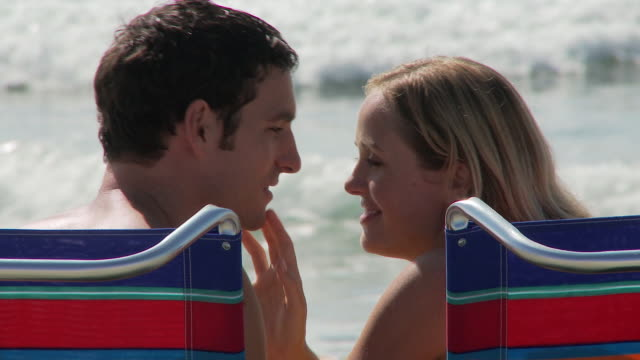 close up of couple kissing in beach chairs at waters edge at the beach - swimming shorts stock videos & royalty-free footage