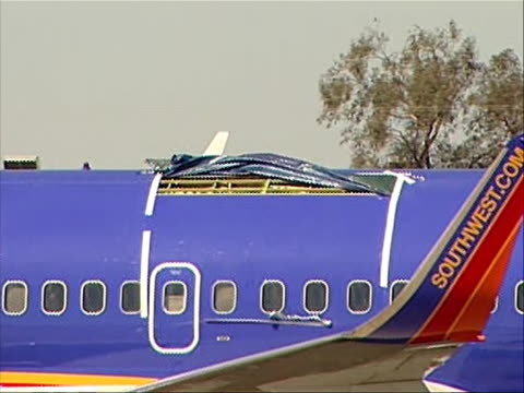 close up of covered hole in fuselage in damaged southwest plane that made an emergency landing in yuma, arizona on april 1, 2011 due to structural... - südwesten stock-videos und b-roll-filmmaterial