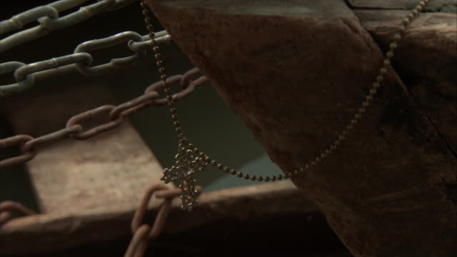 Close up of cucifix chain hanging on bow of canoe