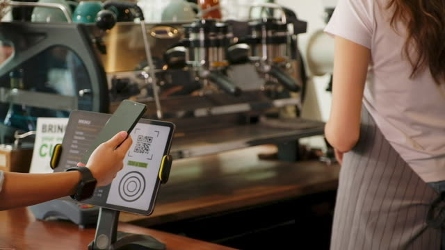 close up of  customer hand making contactless payment through smart phone to buy take away coffee at counter bar in coffee shop cafe, slow motion - paying stock videos & royalty-free footage