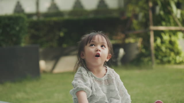 close up of cute asian girl is talking to her parent beside her brother at the garden - black hair stock videos & royalty-free footage
