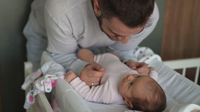 vidéos et rushes de fermez-vous vers le haut du papa embrassant la fille nouveau-née de chéri - chambre de bébé