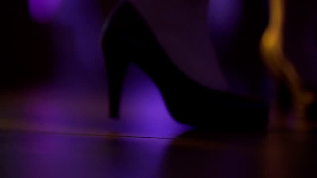 Close up of dancing women and men's feet on the dance floor at the night club or discotheque. Crowd women with beautiful legs in high heels dancing.