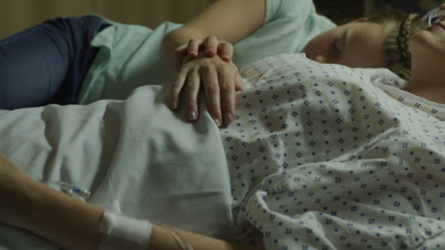 close up of daughter laying in hospital bed sleeping with resting mother / salt lake city, utah, united states - visit stock videos & royalty-free footage