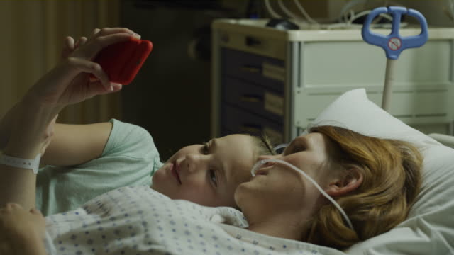 Close up of daughter laying in hospital bed with resting mother watching cell phone video / Salt Lake City, Utah, United States