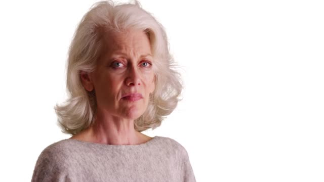 stockvideo's en b-roll-footage met close up of depressed older woman turning to frown at camera on white background - vaste stof