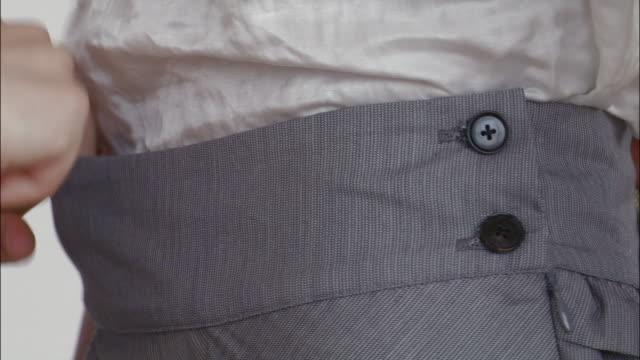 Close up of designer's hands fitting skirt on model