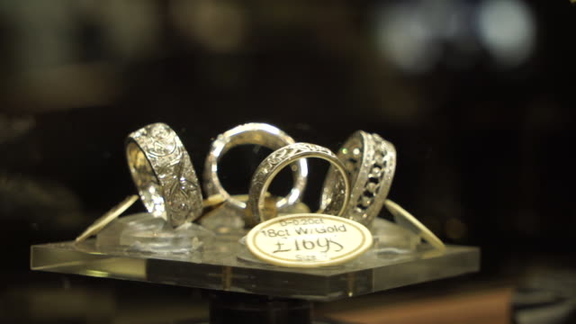 close up of diamond rings on rotating stand in jewellery shop window in hatton garden london - stone object stock videos & royalty-free footage