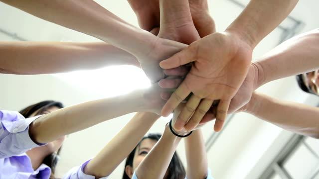 stockvideo's en b-roll-footage met close up van uiteenlopende mensen bedrijfsgroep hand in hand samen, zakenlieden en zakenvrouwen hand zetten samen als teamwork - aan elkaar bevestigd