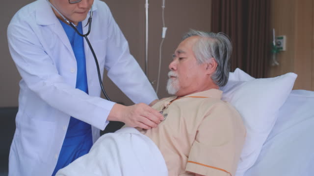close up of doctor come to visit patient in hospital room and talking about the disease of senior man. then use stethoscope to detect some symptom from patient - 人の肺点の映像素材/bロール