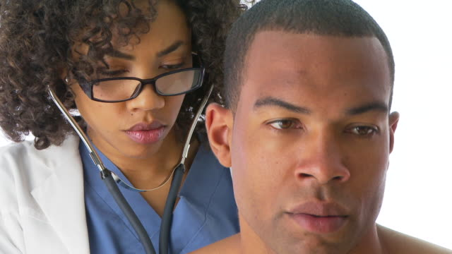 close up of doctor examining patient with stethoscope - untersuchungskittel stock-videos und b-roll-filmmaterial