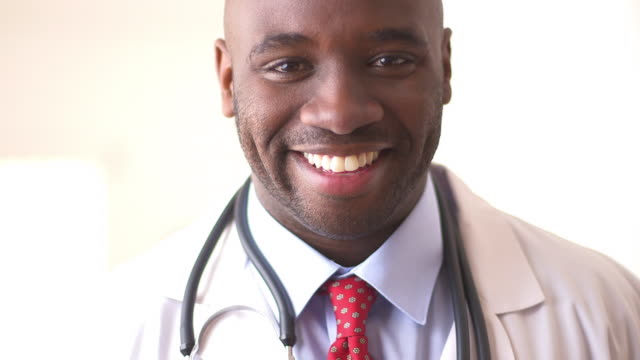 close up of doctor smiling - kopfbild stock-videos und b-roll-filmmaterial