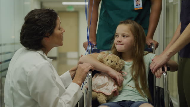 close up of doctor talking to girl in wheelchair and mother in hospital / salt lake city, utah, united states - teddy bear stock videos and b-roll footage