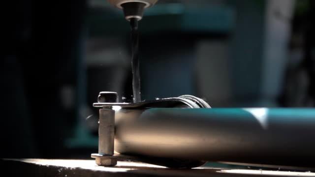 vídeos de stock e filmes b-roll de close up of drilling a hole in steel, slow motion - afiar