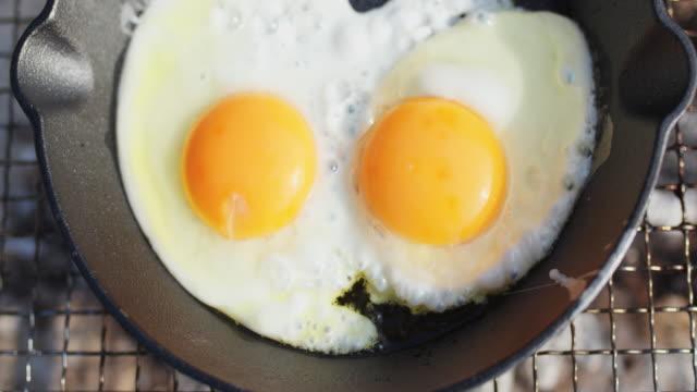 stockvideo's en b-roll-footage met sluit omhoog van eieren die in een koekenpan op de barbecue frituren - gebakken ei