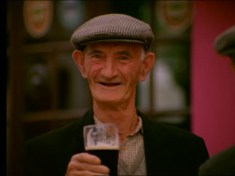 stockvideo's en b-roll-footage met close up of elderly irish man holding glass of ale + smiling - alleen één seniore man