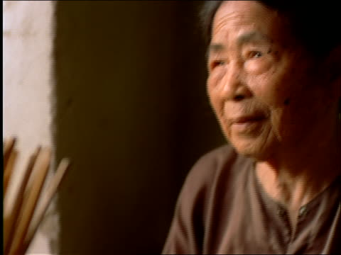 vídeos de stock, filmes e b-roll de close up of elderly woman sitting at table by window / vietnam - só uma mulher idosa