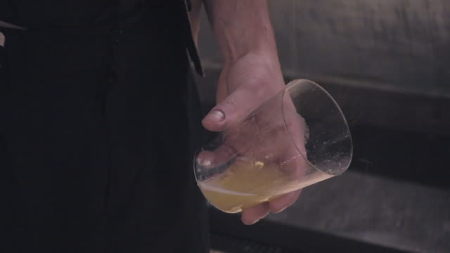 4K | Close up of escanciar sidra / cider pour in a glass. Traditional way to serve apple cider in Asturias (Spain). We can see a man's hand holding a glass meanwhile with the other hand is pouring a bottle from a high level to get better taste.