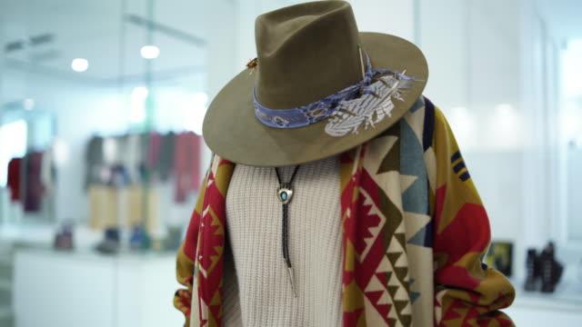 close up of ethnic clothing in a store - copricapo abbigliamento video stock e b–roll