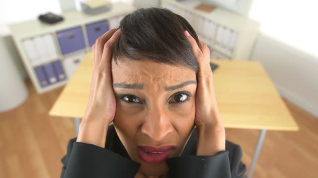 Close up of extremely frustrated business woman screaming at work