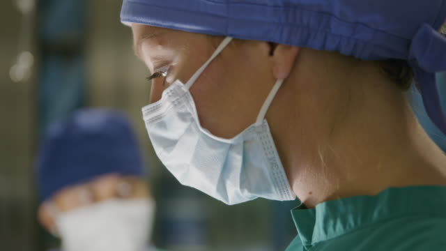 close up of face of nurse handing equipment to surgeon in operating room / salt lake city, utah, united states - surgeon stock videos & royalty-free footage
