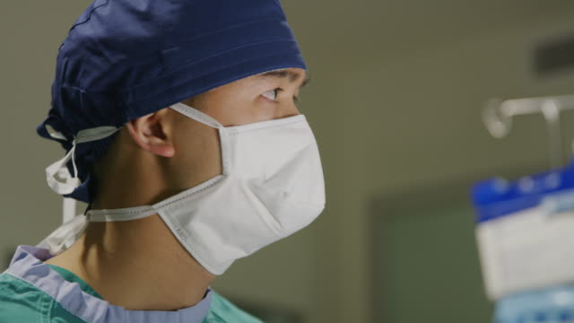 close up of face of nurse looking away in operating room / salt lake city, utah, united states - surgeon stock videos & royalty-free footage