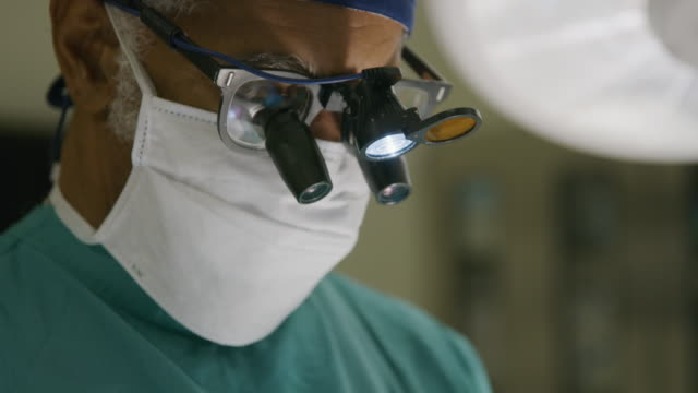 close up of face of surgeon looking down in operating room / salt lake city, utah, united states - operating stock videos & royalty-free footage