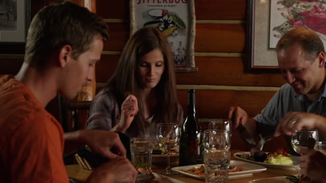 Close up of family eating dinner in restaurant / Idaho, United States