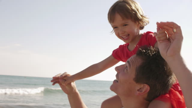 close up of father giving his daughter a shoulder ride/marbella region, spain - tre quarti video stock e b–roll