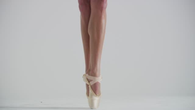 vídeos y material grabado en eventos de stock de close up of feet of woman ballet dancer jumping on pointe in studio - de puntas