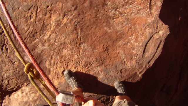 Close up of feet rappelling down edge of steep canyon cliff (POV)