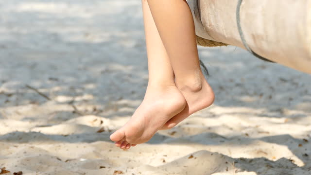 close up of feet swinging in the breeze. - girl sitting cross legged stock videos & royalty-free footage