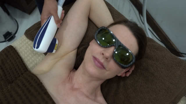 vídeos de stock e filmes b-roll de close up of female adult patient undergoing laser treatment to remove hairs from armpit - depilação