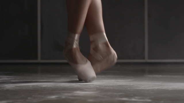 Close up of female ballerina's shoes performing brisé, échappé, entrechat