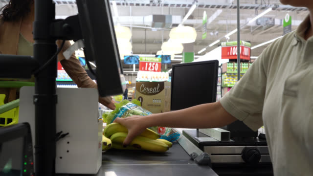 close up of female cashier registering products with bar code reader at check out for female customer at a supermarket - cashier stock videos & royalty-free footage