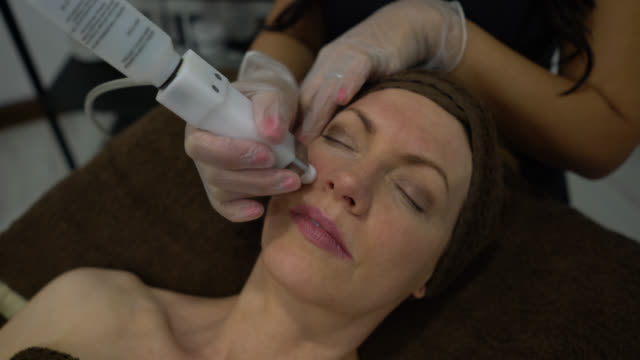 vídeos de stock e filmes b-roll de close up of female customer getting a facial electrotherapy at the spa - spa treatment