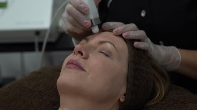 nahaufnahme der weiblichen kundin, die eine laserbehandlung im gesicht im spa erhält - spa treatment stock-videos und b-roll-filmmaterial