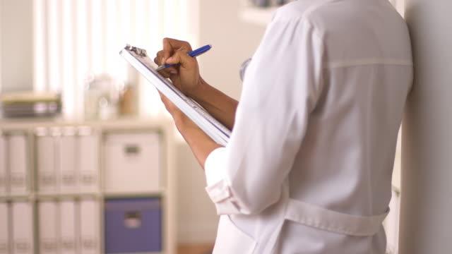 vídeos de stock, filmes e b-roll de close up of female doctor's hands writing on chart - burocracia