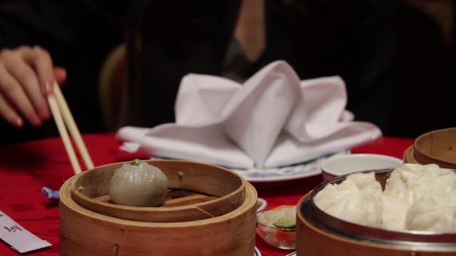 Close up of female eating dim sum in Chinese restaurant