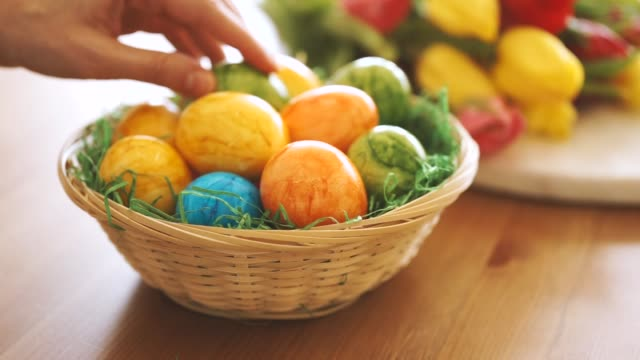 close up of female hand putting an easter egg into a basket - easter stock videos & royalty-free footage