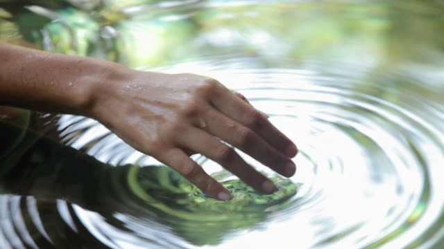 close up of female hand touching water - touching stock-videos und b-roll-filmmaterial