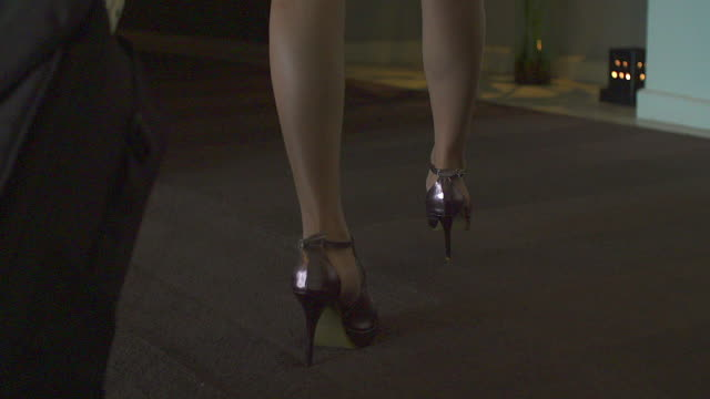 vídeos de stock e filmes b-roll de close up of female legs of a worker walking in the hotel. the woman is wearing formalwear and shoes on high heels. - mulher sedutora