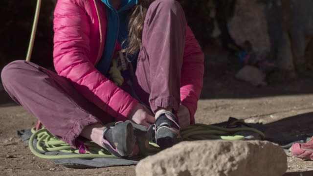 close up of female rock climber putting on the shoes ready for action in the pyrenees - climbing equipment stock videos & royalty-free footage